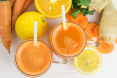 Two mugs with carrot smoothie with a straw on a white wooden table top view. stock photos
