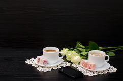 Two mugs of coffee with milk, smartphone, Turkish delight on a saucer, white roses on a black background. Royalty Free Stock Photos