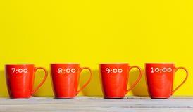 Set of coffee or tea mugs, red on yellow background. Two mugs of coffee or tea in bold color setting with red on yellow background and shadow Stock Photos