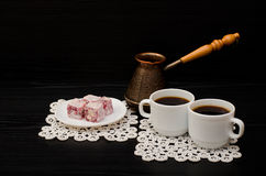 Two mugs of coffee, Turkish delight and cherry pots on a black background Royalty Free Stock Photography