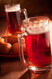 Two mugs filled with beer and hot sausages Royalty Free Stock Photo