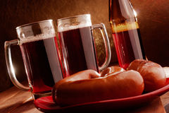 Two mugs filled with beer and hot sausages Stock Images