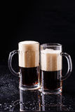 Two mugs of foamy beer Stock Photo
