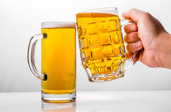 Two Mugs of fresh beer with cap foam Stock Image