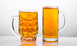 Two Mugs of fresh beer with cap foam Royalty Free Stock Image