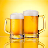 Two Mugs of fresh beer with cap of foam,  on yellow Stock Photo