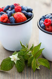 Two mugs with fresh berries on the wooden table.  royalty free stock image