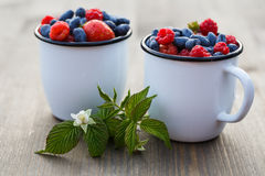 Two mugs with fresh berries on the wooden table.  stock images