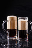 Two mugs of frothy beer. On black background Stock Images