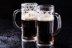 Two mugs of frothy beer. On black background Stock Image