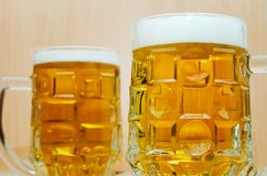 Two mugs full with beer, closeup stock photography