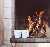 Two mugs near the fireplace Stock Photography