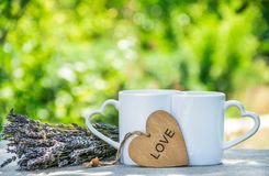 Two mugs of tea in the garden. Romantic morning coffee. Mug with a heart. Royalty Free Stock Image