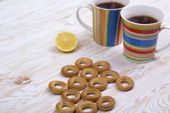Two mugs of tea, lemon and small dry bagels Royalty Free Stock Images