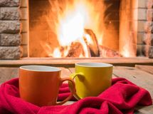 Two  mugs  for tea,  wool things near cozy fireplace. Royalty Free Stock Photography