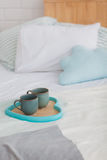 Two mugs on a tray white bed, breakfast concept. Two blue mugs on a tray white bed, breakfast concept Stock Image