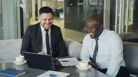 Two multi ethnic businessmen looking at laptop computer and laughing in glassy cafe. African American businessman and. Two multi ethnic businessmen looking at stock footage