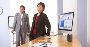 Two multi-ethnic businesswoman standing in office Stock Image