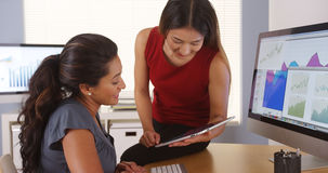 Two multi-ethnic businesswomen talking with tablet at desk Royalty Free Stock Photos