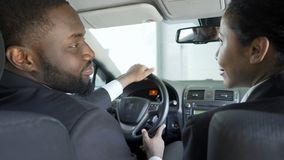 Two multi-ethnic colleagues flirting, discussing business in car, having affair. Stock footage stock video footage