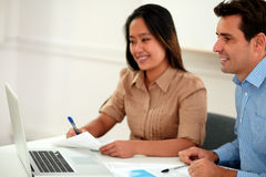 Two multi ethnic colleagues working on documents Royalty Free Stock Photography