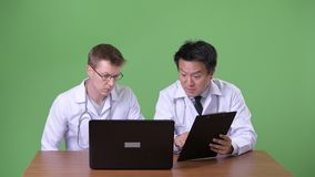 Two multi-ethnic doctors together against green background. Studio shot of mature Japanese man doctor and young Scandinavian man doctor together against chroma stock footage