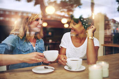 Two multi ethnic friends enjoying coffee. Together in a coffee shop viewed through glass with reflections as they sit at a table chatting and laughing Royalty Free Stock Images