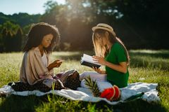 Two multi-ethnic girl friends during the picnic on the sunny meadow. The attractive african girl is chatting and. Browsing via the mobile phone while her pretty Royalty Free Stock Photo