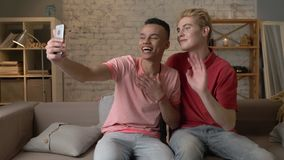 Two multi-ethnic homosexual friend sitting on the couch, embracing and showing a greeting gesture in a video chat. Happy. LGBT couple concept, gay lovers. 60 stock video