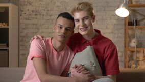 Two multi-ethnic homosexual friends sit on the couch holding hands, hugging, smiling, looking at the camera. Home. Cosiness, family, internet concept. 60 fps stock video footage