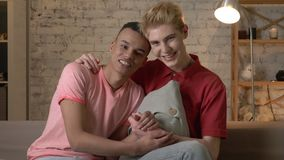 Two multi-ethnic homosexual friends sit on the couch holding hands, hugging, smiling, looking at the camera. Home. Cosiness, family, internet concept. 60 fps 4k stock video