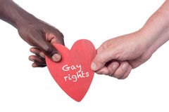 Two multi racial hands. Two multi racial men holding a gay rights wooden heart Royalty Free Stock Photography