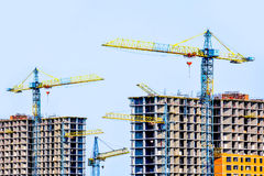 Two multi-storey buildings under construction. Many cranes. Construction of modern housing. Building bussiness Royalty Free Stock Images