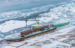 Two multicolor fishing boats trapped on frozen river Danube Royalty Free Stock Images