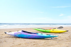 Two multicolored canoes on the beach Stock Photos