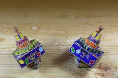 Two multicolored Hanukkah dreidels on a wood tabletop with space for text royalty free stock images