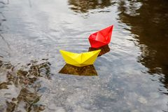 Two multicolored paper boats floating on a stream royalty free stock image