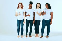 Two multicultural couples of women in casuals looking happy together on white stock photo