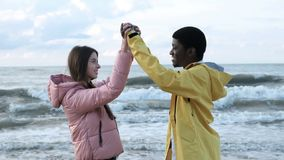 Friends having fun together on the beach slow mo. Two multicultural free person of black male and attractive european female. Lovers clap hands slow motion. They stock video footage