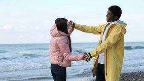 Friends having fun and enjoy together on the beach. Two multicultural person of trendy black male and attractive cute female slowmo. Lovers keep each other and stock footage