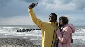 Friends taking selfie at phone on coast closeup. Two multicultural persons of black guy and caucasian female making a photography at smartphone. Positive funny stock video