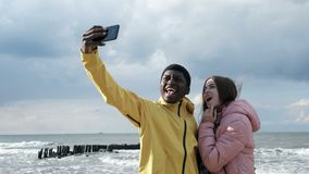 Friends taking selfie at phone near the sea. Two multicultural persons of black guy and cute white lady shoot a photography at smartphone closeup. Positive funny stock video footage