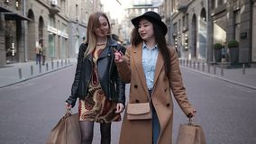 Two multiethnic girlfriends shopping together. Two charming multiracial girlfriends carrying shopping bags while walking along cobblestone street after good day stock video