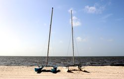 Two multihull small Catamarans moored on a secluded beach in Biloxi, Mississippi. Royalty Free Stock Photo