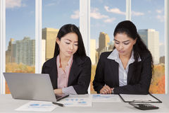 Two multiracial businesswomen discussing in office Royalty Free Stock Image