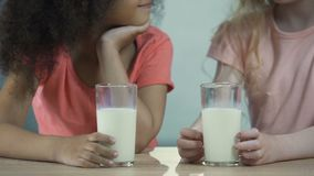 Two multiracial girls holding glasses of milk and showing tongue to each other. Stock footage stock video footage