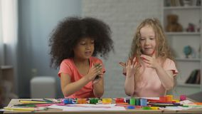 Two multiracial kids sitting at the table and smudging hands with paints stock footage
