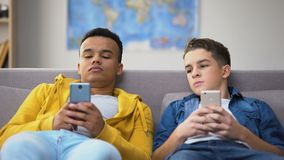 Two multiracial male teenagers surfing social nets, replacing live communication. Stock footage stock video