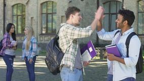 Two multiracial men talking and giving high five each other. Students life. Stock footage stock footage