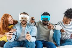Two guys playing video games using VR glasses and girlfriends support them. royalty free stock images